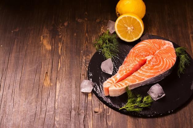 Сырой стейк из лосося с лимоном и зеленью