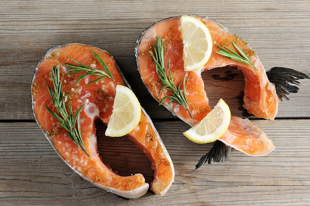 Raw salmon steak with lemon and rosemary on wooden boards