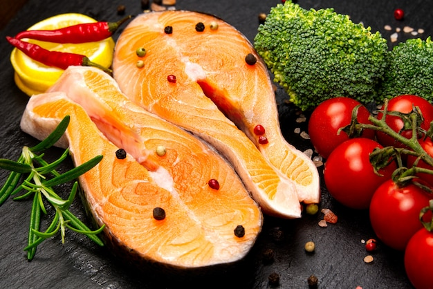 Raw salmon steak on wooden board close up