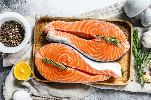 Raw salmon steak on a wooden tray with spices. healthy seafood. gray background. top view