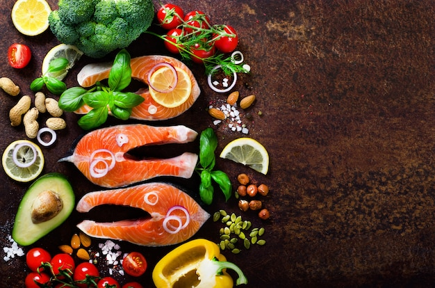 Raw salmon steaks, aromatic herbs, onion, lemon, salt and fresh vegetables for cooking