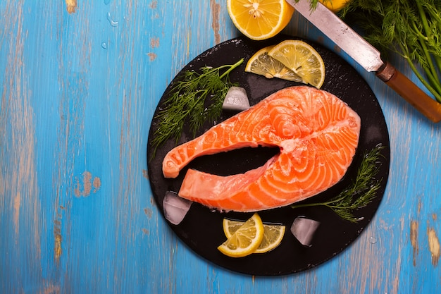 Raw salmon steaks and ingredients on slate.