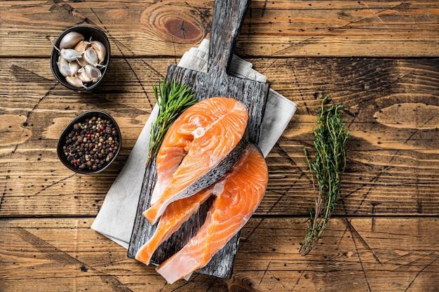 Сырые стейки лосося на деревянной разделочной доске с тимьяном и розмарином. деревянный фон. вид сверху.