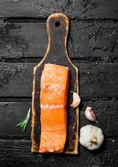 Сырые стейки из лосося с чесноком и розмарином. на черном деревенском.