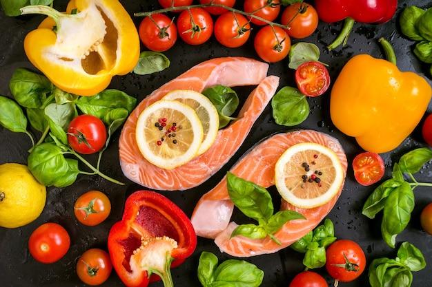 生のサーモンステーキにレモンスライスとフレッシュチェリートマト、ピーマン、バジルの葉、ドライペッパーを添えて。