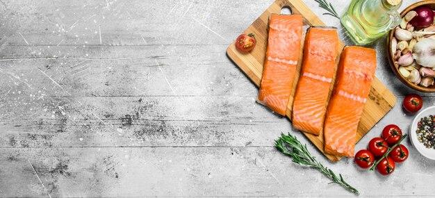Сырые стейки лосося с помидорами на разделочной доске.