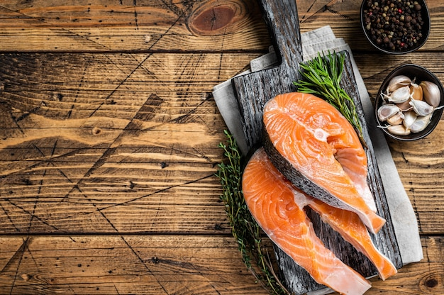 Raw salmon steaks on a wooden cutting board with thyme and rosemary. wooden background. top view. copy space.