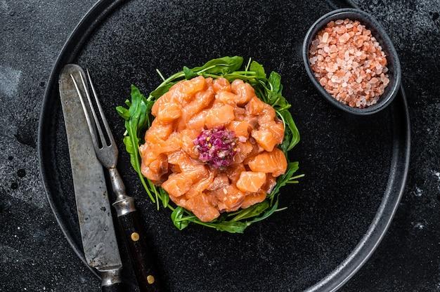 검은 접시에 붉은 양파, 아루굴라, 케이퍼를 곁들인 생 연어 타르타르 또는 타르타르