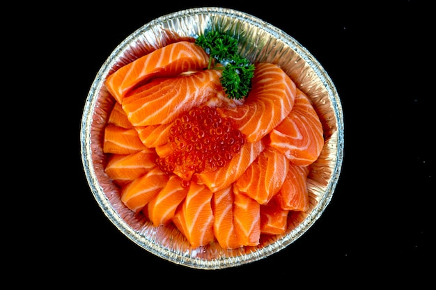 Raw salmon topping with broccoli put in foil plate, top view in soft focus