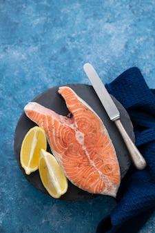 Сырой лосось с лимоном на черной керамической доске