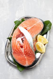 Сырой лосось с лимоном на блюде на керамике