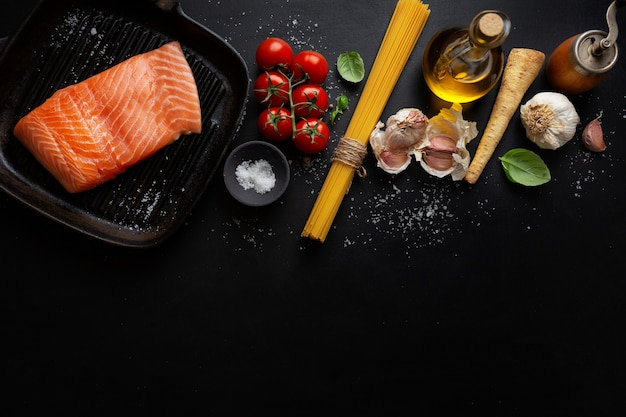 Сырой лосось с макаронами спагетти и специями на темной поверхности