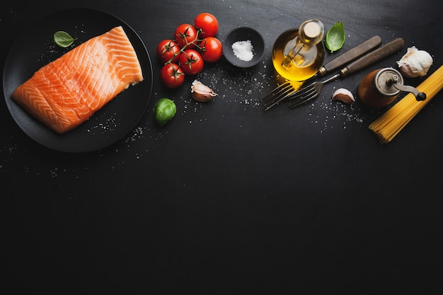 Raw salmon with spaghetti pasta and spices on dark background. top view
