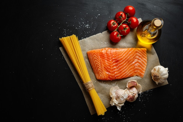 Raw salmon with spaghetti pasta and spices on dark surface