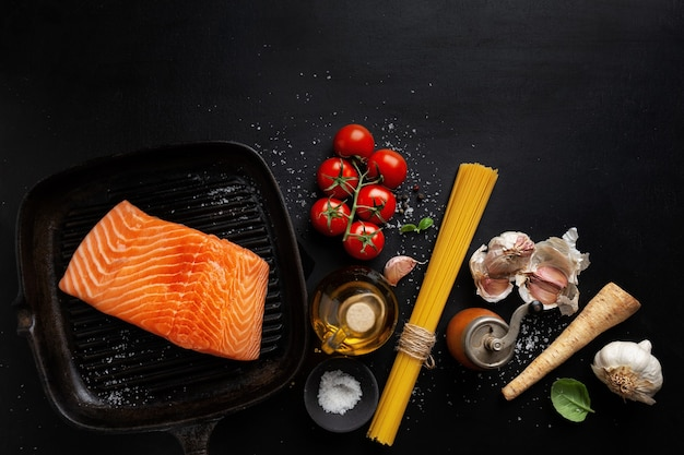 Raw salmon with spices on dark surface