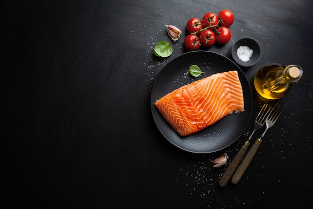 Raw salmon with spices on dark table. top view