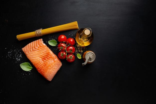 Сырой лосось со специями на темной поверхности