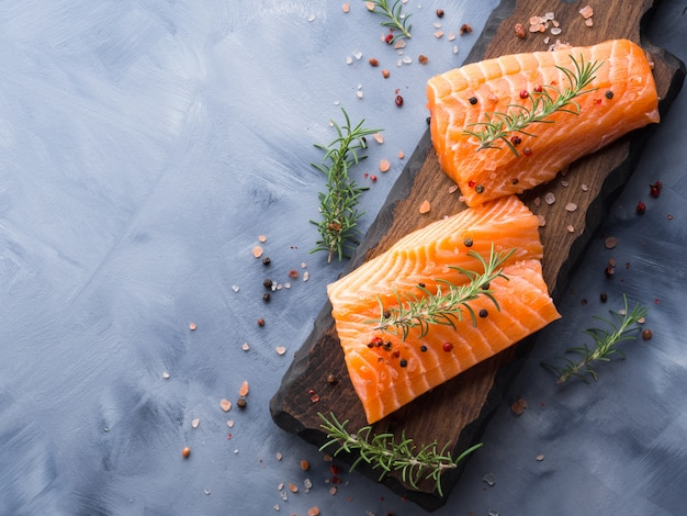 Raw salmon on wooden board with herbs