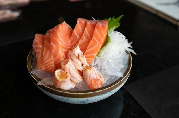 Сырой сашими нарезанный лосось и копченый лосось на льду в миске в японском ресторане