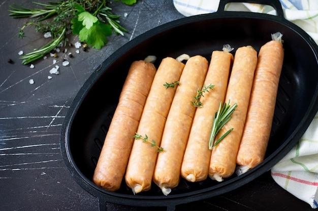 Сырая колбаса на сковороде гриль кастирон с зеленью и специями на темном каменном фоне купаты