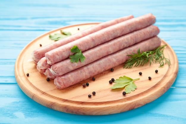 Сырая колбаса на разделочной доске. вид сверху