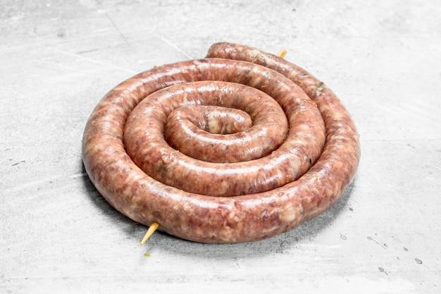Сырая колбаса с говядиной и свининой. на деревенском фоне.