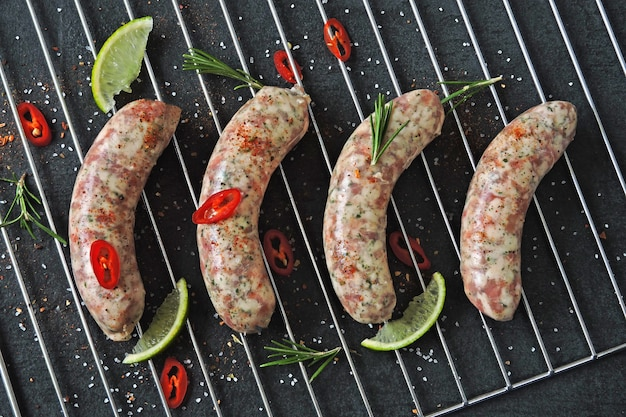 Raw sausage with spices on the grill grate. unprepared bavarian sausages.
