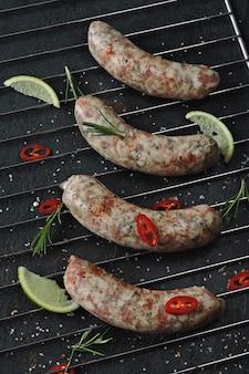 Сырая колбаса со специями на решетке гриля. неподготовленные баварские колбаски.