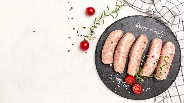 Сырые колбасы и ингредиенты для приготовления. мюнхенские колбаски из телятины. баннер, меню, место рецепта для текста, вид сверху.