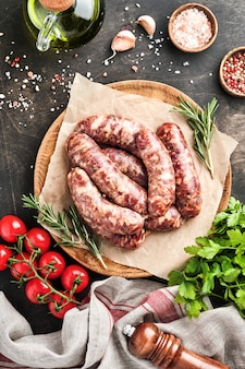 Raw sausages or bratwurst and ingredients for cooking on dark stone background. top view with copy space.