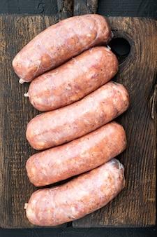 Raw sausages on dark background
