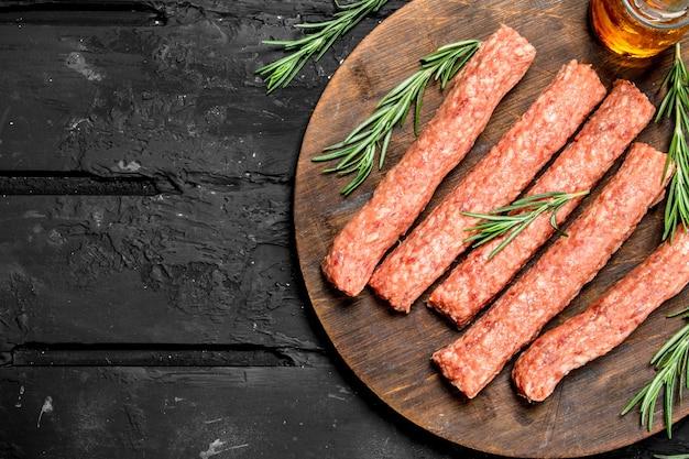 소박한 테이블에 로즈마리와 쇠고기에서 원시 소시지.