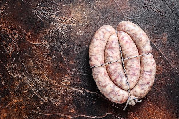 Сырые колбаски из свинины и говядины на деревянной доске