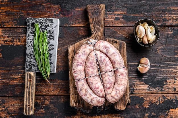 Сырые колбаски из свинины и говядины на деревянной разделочной доске