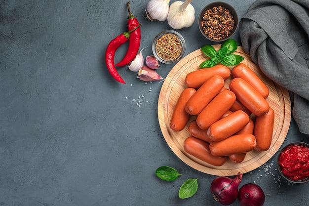 Сырые сосиски на разделочной доске на сером фоне с ингредиентами. вид сверху, копия пространства.