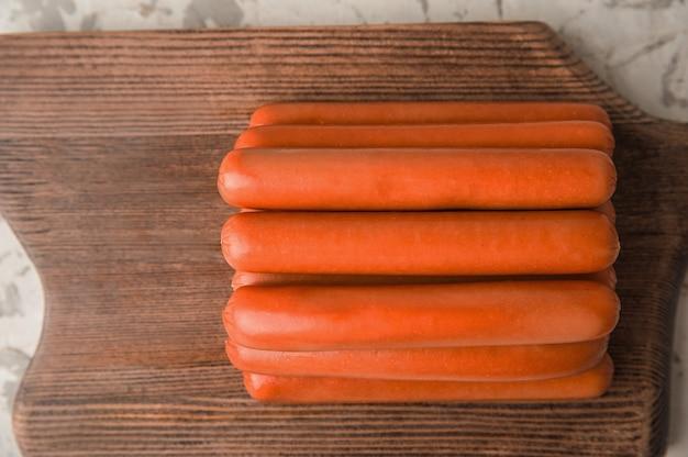 Сырые сосиски на деревянной доске