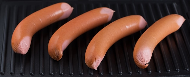 Сырые колбаски на поверхности гриля
