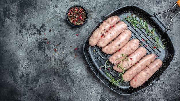 Сырые колбаски с зеленью и специями. кетогенная диета, вид сверху. место для текста.