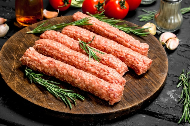 Raw sausages with herbs and tomatoes. on black rustic.