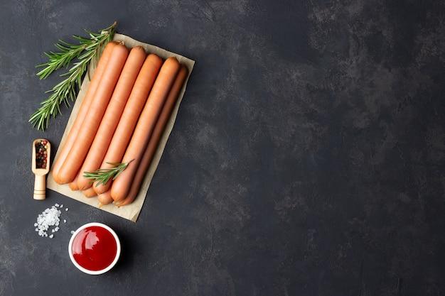 Сырые сосиски с кетчупом на разделочной доске.