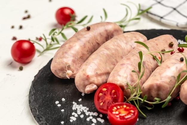 Сырые сосиски со специями и розмарином. предпосылка рецепта еды. закройте вверх.