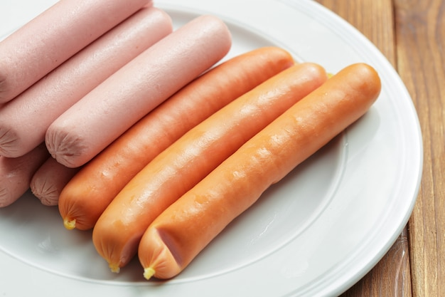 Raw sausages on wooden table