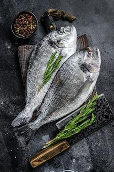 Сырая рыба дорадо морского леща на разделочной доске. черный фон. вид сверху.