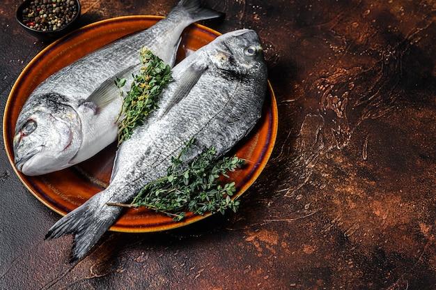 Сырая рыба морского леща и ингредиенты для приготовления. темный фон. вид сверху. скопируйте пространство.