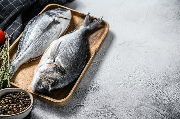 Raw sea bream fish with cooking ingredients, cherry tomatoes, thyme, pepper. gray background. top view.  copy space