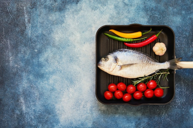 Raw sea bream fish with vegetables in pan on blue background. top view, copy space. mediterranean seafood concept.
