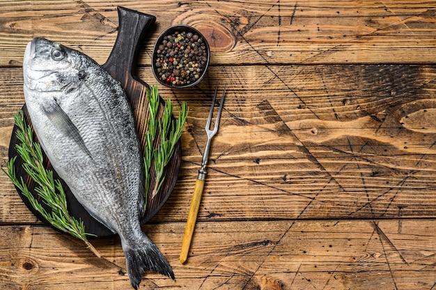 Сырой морской лещ или морская рыба дорадо со специями и зеленью на разделочной доске. деревянный фон. вид сверху. скопируйте пространство.