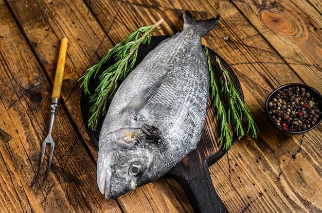 Сырой морской лещ или морская рыба дорадо со специями и зеленью на разделочной доске. деревянный фон. вид сверху.