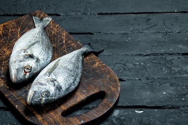 Сырая морская рыба дорадо на разделочной доске. на черном деревенском.