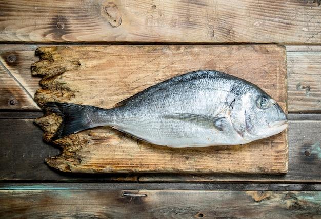 まな板の上に生の海魚ドラド。木製の背景に。